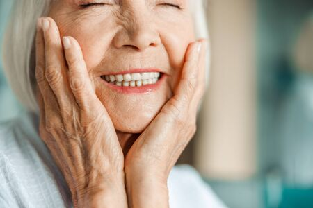 Joyful elderly lady touching her face and smiling Standard-Bild