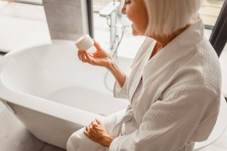Old woman sitting in the edge of bathtub and looking at cosmetic product stock photo 版權商用圖片 - 137150082