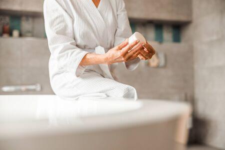 Elderly woman in bathrobe holding jar of cream