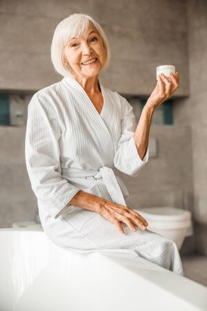 Cheerful elderly woman holding jar of cream