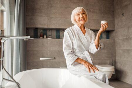 Smiling elderly woman holding jar of cream 版權商用圖片