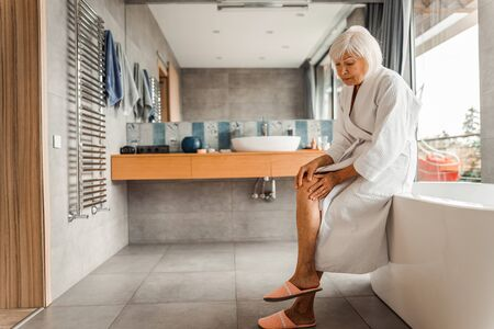 Unhappy old lady feeling pain in her knee