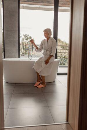 Cheerful senior lady in bathrobe holding jar of cream