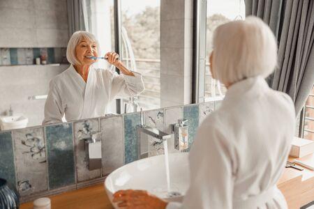Schöne alte Dame beim Zähneputzen im Badezimmer