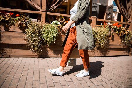 Senior lady in sneakers walking on the street