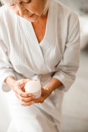 Old lady in bathrobe looking at skincare cosmetic product stock photo 版權商用圖片 - 137151045