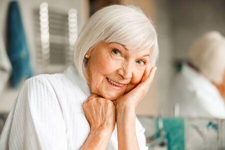 Cheerful elderly woman propping up head on hand Standard-Bild