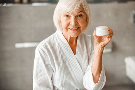Cheerful old lady holding jar of cream