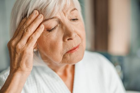 Unhappy elderly lady touching forehead and having headache