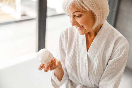 Lovely old woman looking at cosmetic cream and smiling