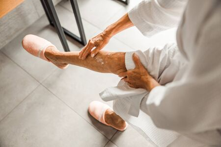 Old woman applying therapeutic cream on leg 版權商用圖片 - 137309786
