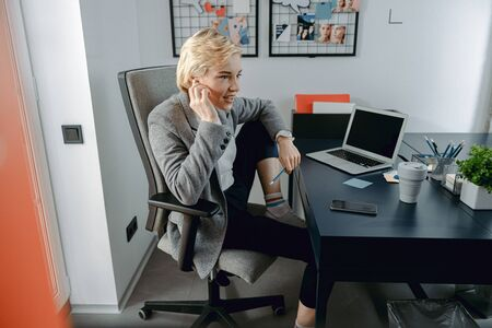 Szczęśliwa młoda kobieta używa słuchawek w miejscu pracy