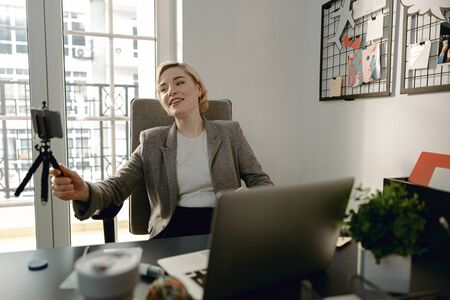 Smiling young woman holding smartphone in the office Reklamní fotografie