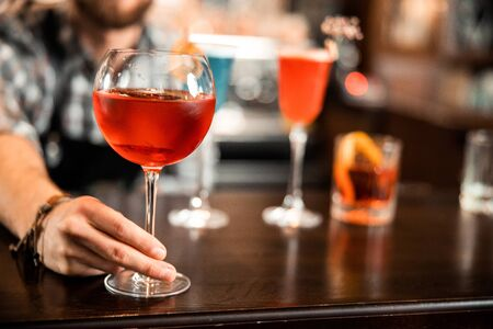 Close up of bartender offering an alcoholic cocktail for visitor stock photo