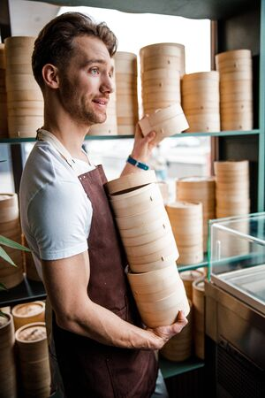 Cute Caucasian waiter is carrying stack of wooden dishes in the cafe 写真素材