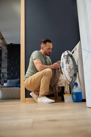 Mann benutzt Waschmaschine stockfoto