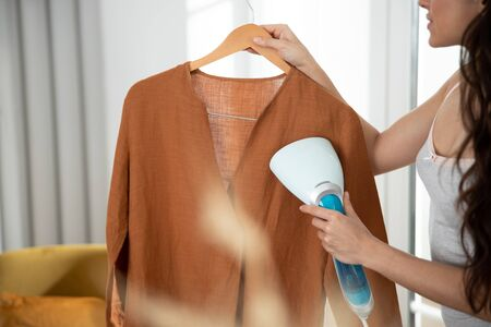 Young lady refreshing shirt with clothes steamer