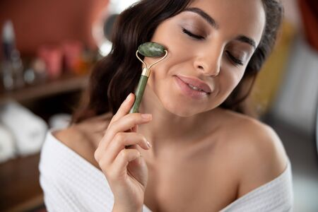 Charming young woman using face massager and smiling Stock fotó