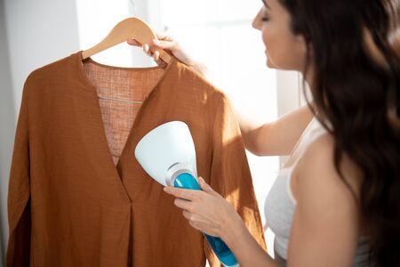 Señorita con vaporizador de ropa para refrescar la camisa Foto de archivo