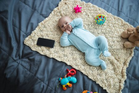 Cute newborn kid with toys at home