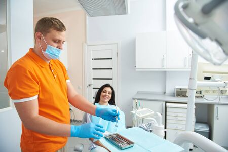 Stomatologist is preparing instruments for treatment teeth