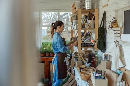 Focused female herbalist staring at glass jars