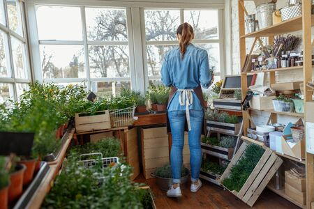 Young woman cultivating flowers and herbs indoors