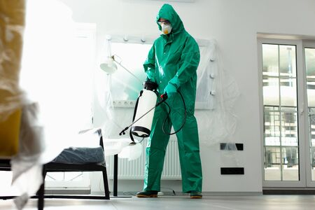 Man in chemical costume working on the sanitation stock photo