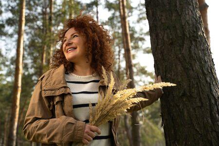 Charming lady with beautiful bouquet standing near tree Фото со стока