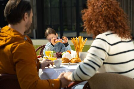 Adorable little girl eating donut while sitting at the dinner table with mother and father stock photo