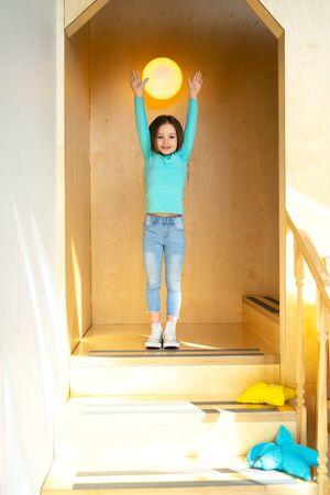 Cute little girl standing in children playroom 写真素材