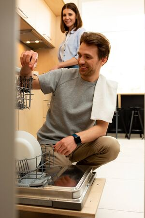 Happy man using dishwasher in the kitchen Stock Photo