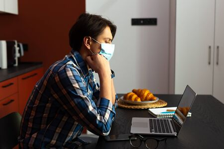 Man with gadgets wearing sterile mask at home Stock Photo
