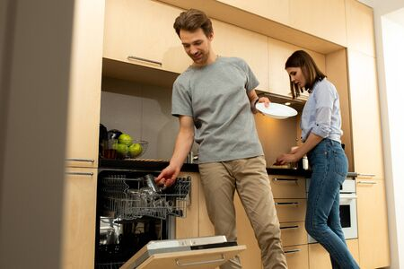 Male putting dishes into dishwasher at home