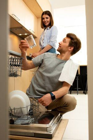 Happy male taking dishes out of dishwasher