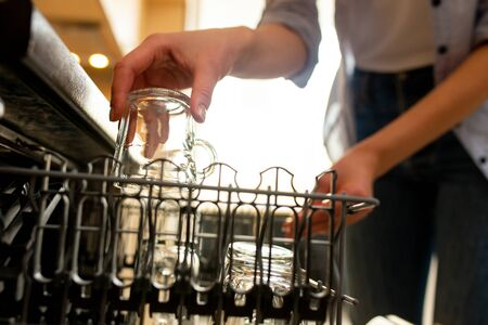 Close up of woman putting glass into a dishwasher