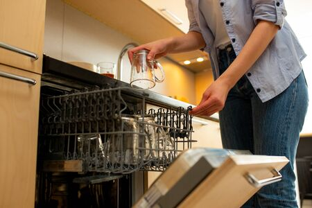 Cropped photo of young woman in casual clothes is putting dishes into a dishwasher at her modern kitchen at home