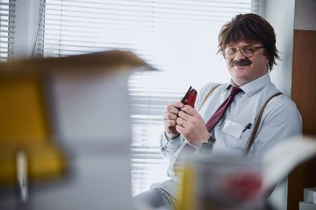 Funny mirthful man sitting with stapler and smiling