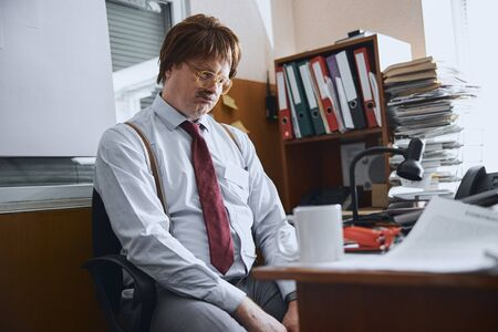 Sad mature male person sitting at his desk pursing his lips