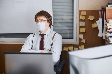 Tired aged manager spending time in office in protective mask