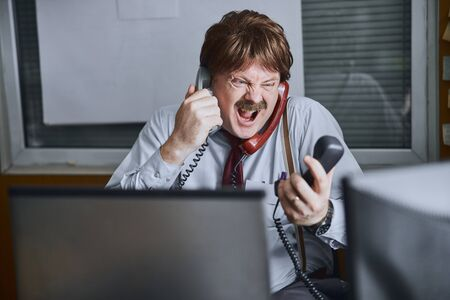 Furious aged manager or clerk unsuccessfully tries to speak by three telephone lines
