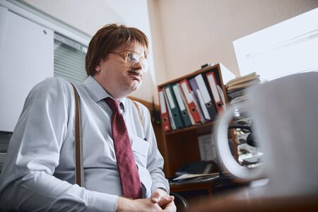 Frustrated aged clerk is being in his office facing life problems