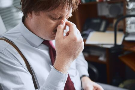 Middle-aged male office worker rubbing his nose tired of glasses Reklamní fotografie