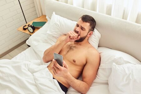 Tired young man using cellphone and yawning