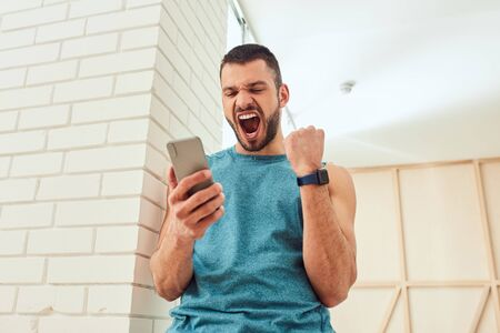 Happy young man holding cellphone and screaming with joy Stockfoto