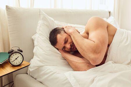Displeased gentleman covering ears while alarm clock ringing