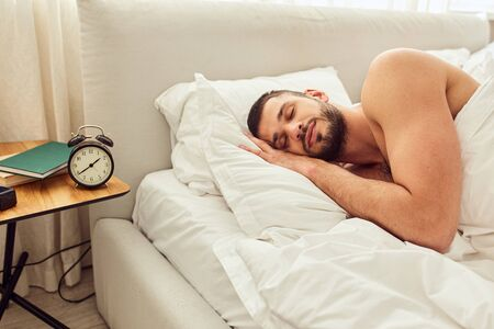 Handsome young man sleeping peacefully in bed