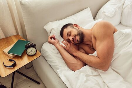 Handsome young man sleeping in bed at home Reklamní fotografie