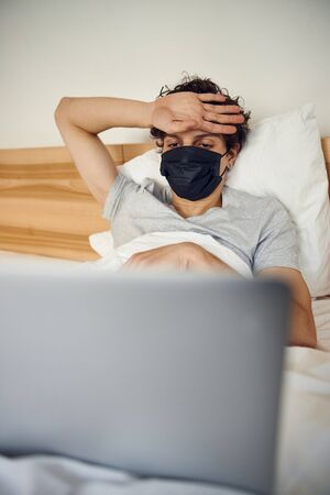 Sick guy in medical mask touching forehead to check fever