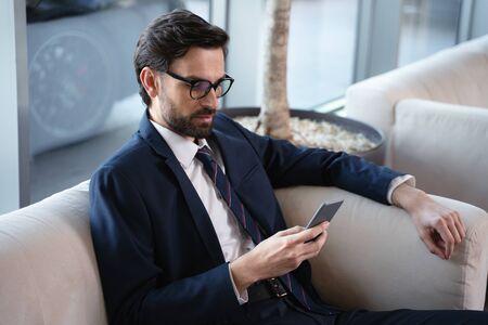 Elegant businessman using smartphone at a hotel lobby